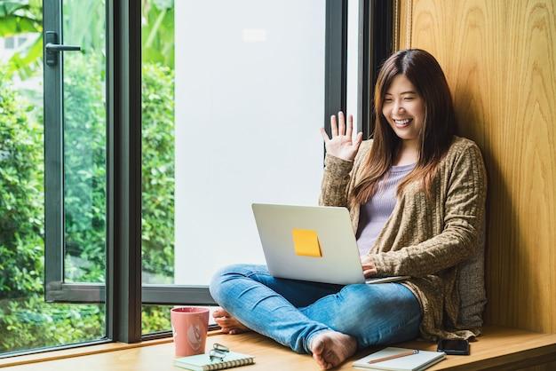 テクノロジーノートパソコンを使用し、挨拶で自宅で仕事をしているアジアのビジネスウーマン