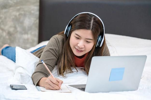 テクノロジーノートパソコンを使用して自宅で仕事のために書くアジアのビジネスウーマン