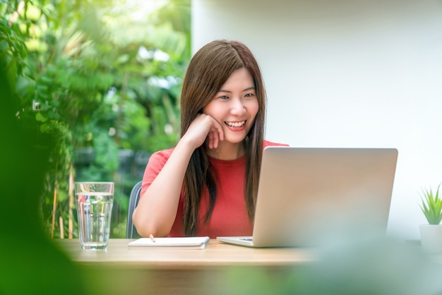 屋外の家や庭で在宅勤務のための技術ラップトップを使用してアジアのビジネス女性