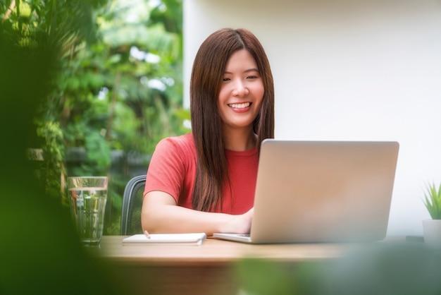 屋外の家で自宅から仕事にテクノロジーラップトップを使用してアジアのビジネスウーマン