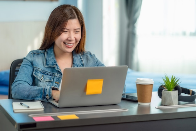 Asian business woman using technology laptop and working from home in indoor bedroom