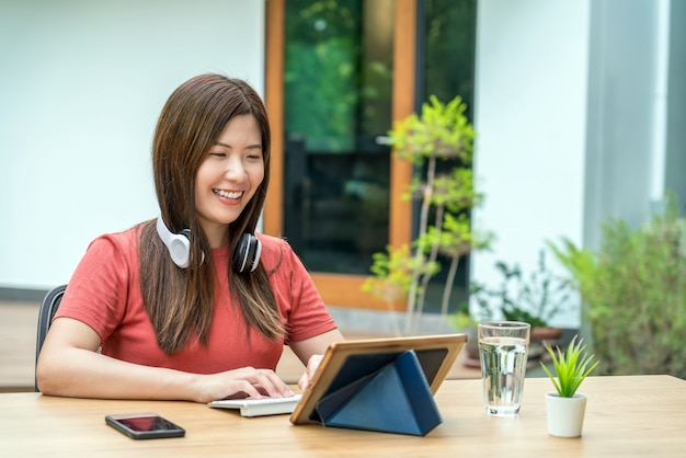在宅勤務のためのキーボードとヘッドフォンを備えたテクノロジータブレットを使用してアジアのビジネスウーマン
