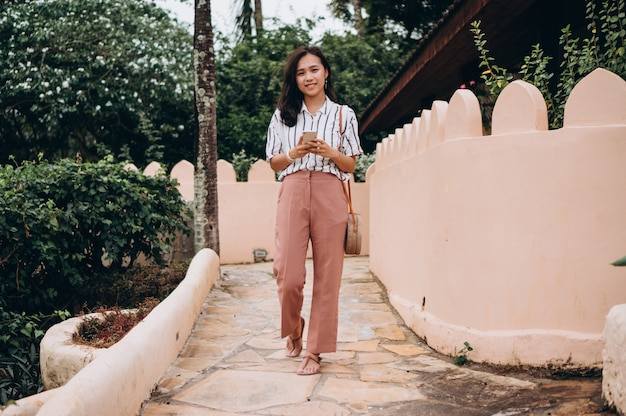 Asian business woman on a vacation talking on phone
