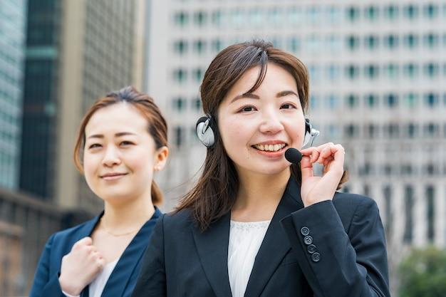 ビジネス地区でヘッドセットを身に着けているアジアのビジネスウーマン