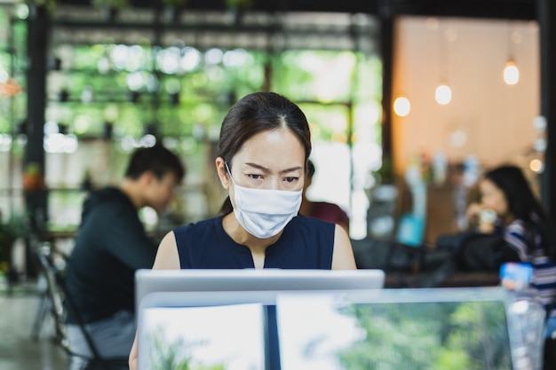 Asian business woman wearing face mask working on laptop.