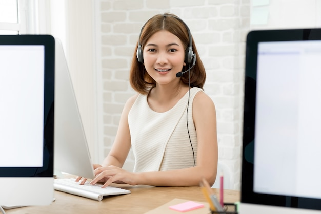 Asian business woman wearing microphone headset working in the office as a telemarketing customer service agent, call center job concept