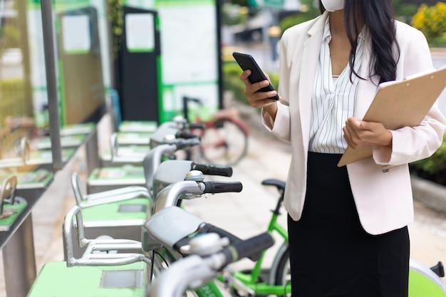 保護フェイスマスクを身に着けているアジアのビジネスウーマンは、屋外で公共の自転車を借りるためにスマートフォンを使用してcovid-19ウイルスを防ぎます。都市環境でのレンタル自転車。