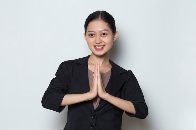 ゲストジェスチャーを歓迎するアジアのビジネスウーマン