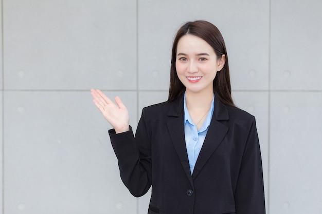 Азиатская деловая женщина в черном строгом костюме улыбается и показывает руку, чтобы что-то подарить