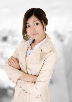 オフィスビルの顔に自信を持って表情を持つアジアのビジネスウーマン。