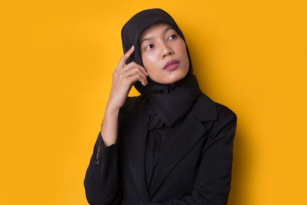 Азиатская деловая женщина с портретом в хиджабе думает, сомневается и смущается