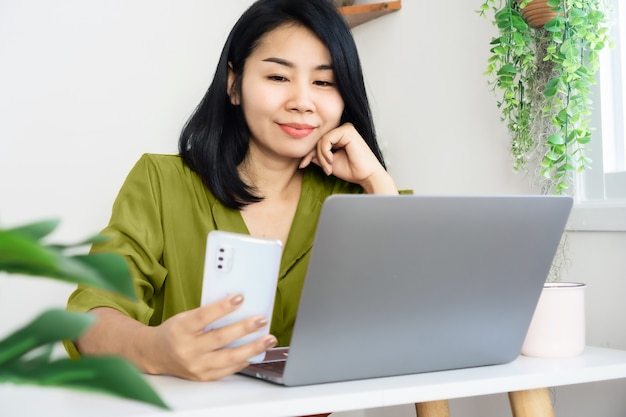 스마트 폰 및 노트북 홈 오피스에서 아시아 비즈니스 여자 작업