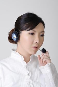働くアジアのビジネス女性、灰色の壁にクローズアップの肖像画。