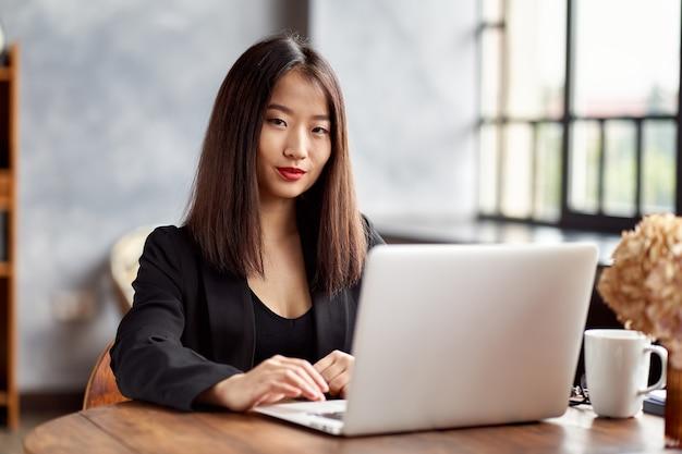 オフィスでラップトップで働くアジアのビジネスウーマン。日本の実業家