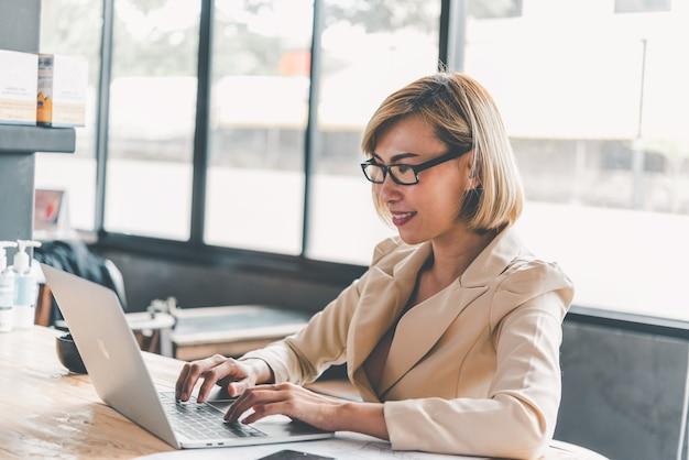 Азиатская деловая женщина, работающая на ноутбуке, ищет в интернете, просматривает информацию, сидя и работая за столом
