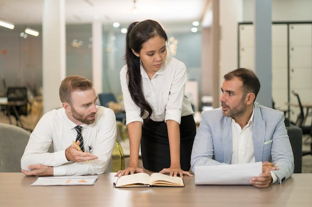 Asian business woman working with coworkers at desk