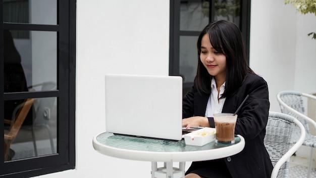 카페에서 자신의 노트북을 사용하는 아시아 비즈니스 우먼