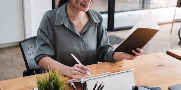ホームオフィスでタブレットを使用して作業しているアジアのビジネス女性。在宅勤務のコンセプト。