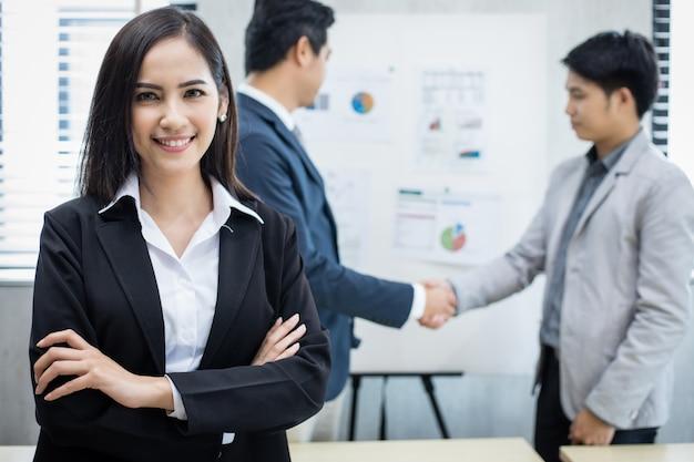 アジアのビジネス女性と会議にノートブックを使用しているグループとビジネス女性が作業に満足して笑顔