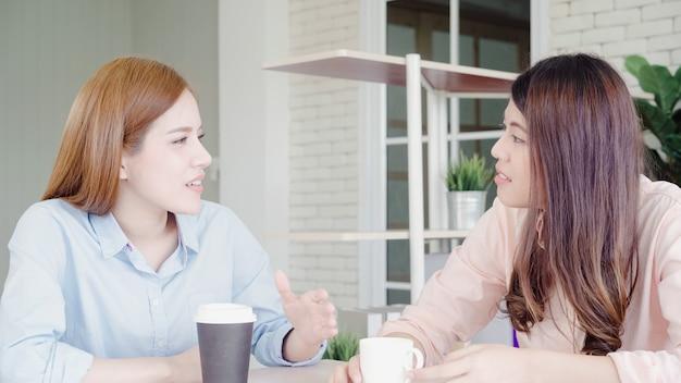 暖かいコーヒーを飲みながら楽しんでいるアジアのビジネス女性、仕事について話し合い、雑談のゴシップ