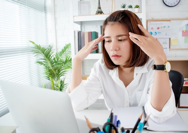 Asian business women have stress and headaches from their work at the office