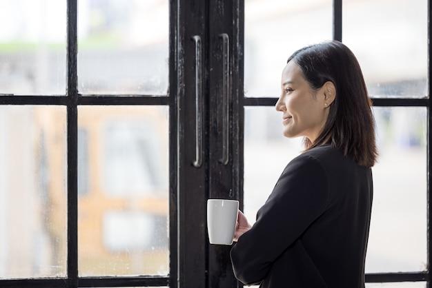 コーヒー カップを持ち、休憩時間にオフィスの窓のそばに立つアジアのビジネス女性