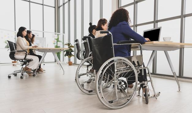 휠체어에 앉아 사무실 탁자에 있는 노트북 작업을 하는 장애인 여성을 포함한 아시아 비즈니스 여성. 비즈니스 회의에 대 한 개념입니다.