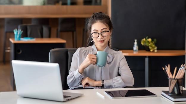 Азиатские деловые женщины сидят в офисе и пьют кофе, глядя на портативный компьютер