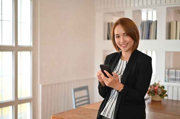 Asian business women standing in office workplace and smile on face.