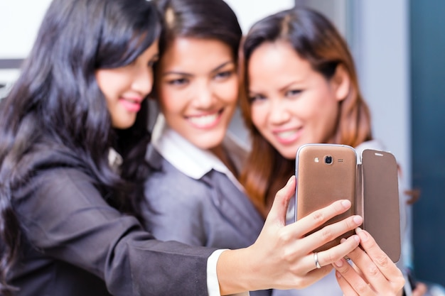 Asian business women taking selfie with smart phone