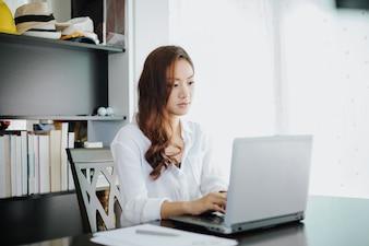 アジアのビジネスの女性は、ノートブックを使用して、笑顔で仕事をする
