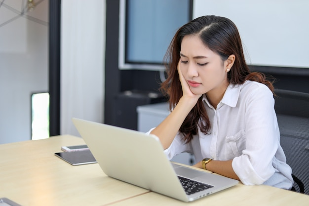 Asian business women using notebook and  serious and headache for working