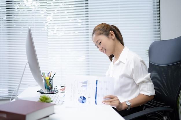 Азиатские бизнес-леди работают в офисах. работая, она была счастлива.