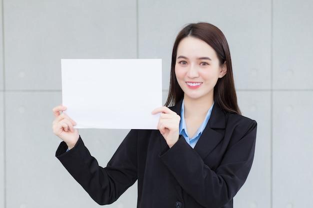 Азиатская бизнес-леди держит простую бумагу (белую бумагу), чтобы что-то представить.