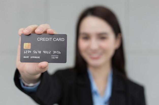 アジアのビジネスワーキングウーマンは、クレジットカードが金融選択の概念で閉じられていることを示しています。