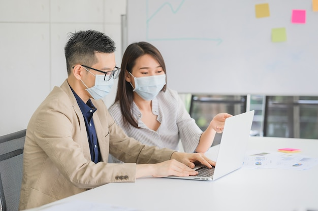 아시아 사업가 및 사업가가 코로나 바이러스 보호를 위해 얼굴 마스크를 착용하고 비즈니스 프로젝트 논의