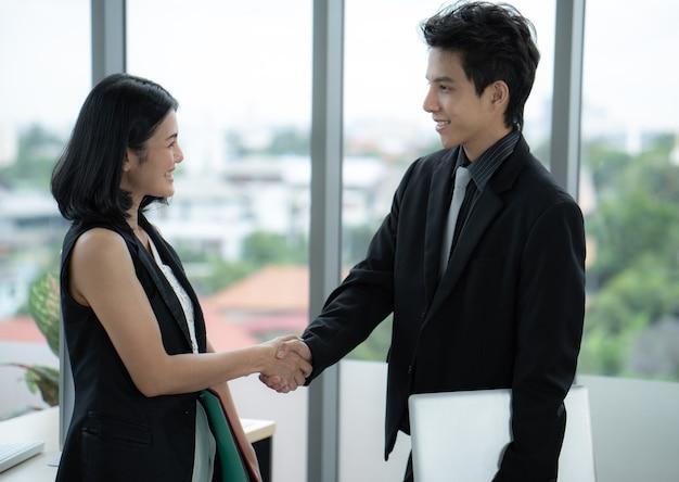 会社の目標に沿って達成された仕事を祝うためにアジアのビジネスマンと女性の握手