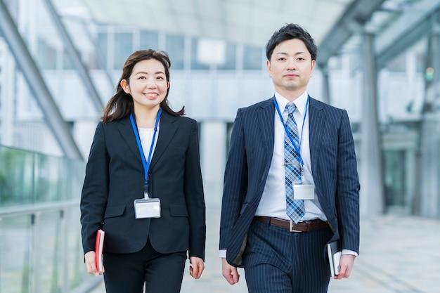 アジアのビジネスマンとスーツを着た女性が並んで歩く