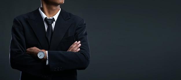 Азиатский бизнесмен скрещенными на темном фоне копией пространства