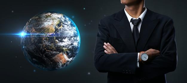暗い背景に地球の横に立っているアジア系のビジネスマンの腕を組んで