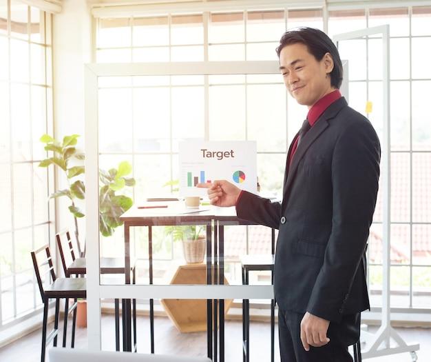 Азиатский бизнесмен как руководитель встречи, давая презентацию точки пальца на графике в конференц-зале в офисе.