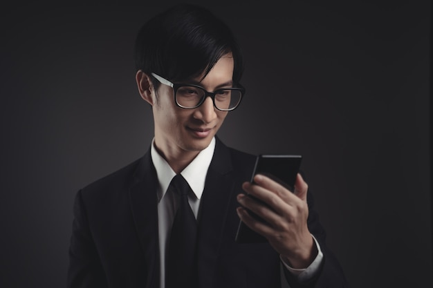 Asian businessman in black suit happy and looking at smart phone.