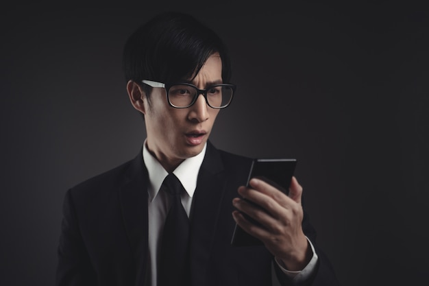 Asian businessman in black suit worried and looking at smart phone.