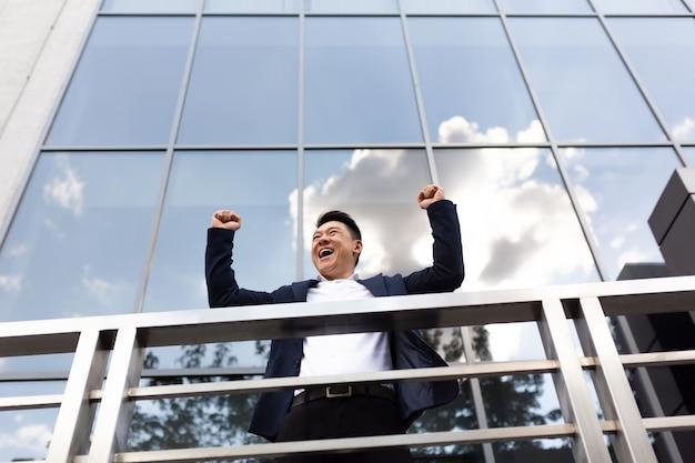 アジアのビジネスマンの上司は、暗い色のビジネススーツでバルコニーの彼のオフィスセンターの近くに立って手を上げて勝利を祝う