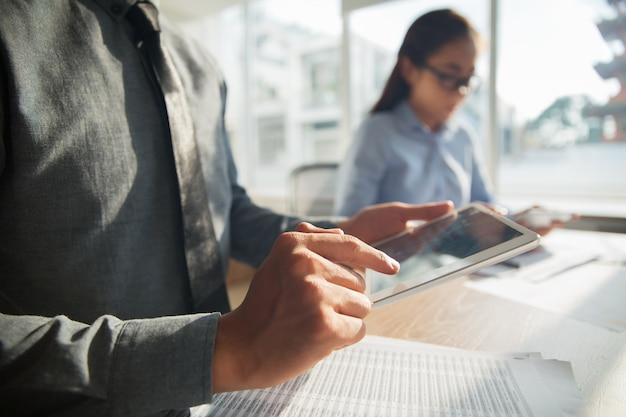 Азиатский бизнесмен просмотра информации о сенсорной панели