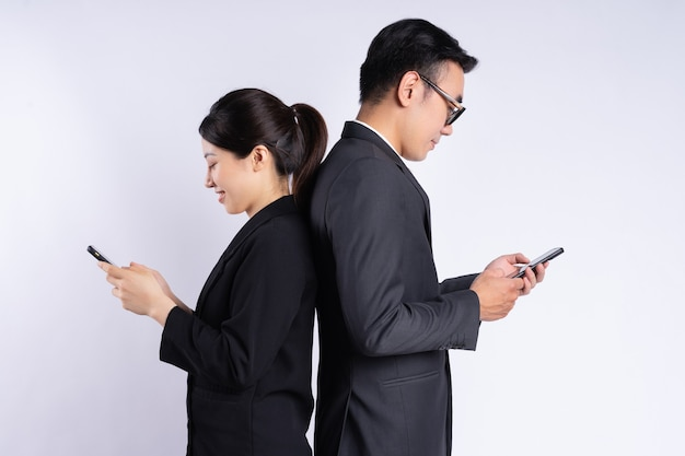 Asian businessman and businesswoman using smartphone on white background