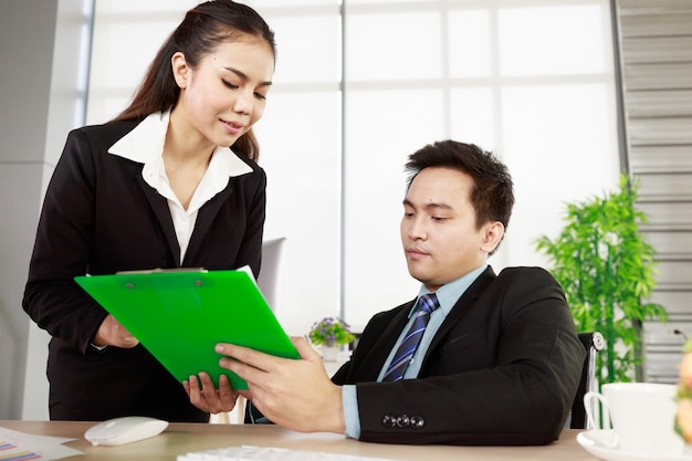 Asian businessman and businesswoman working together in office. concept for teamwork in company.