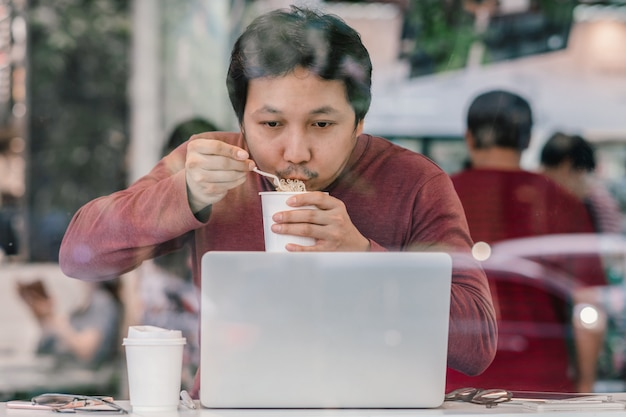 Asian businessman in casual suit eating noodles with urgent action in rush hour at the des