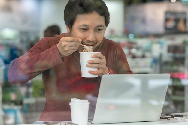 Asian businessman in casual suit eating noodles with urgent action in rush hour