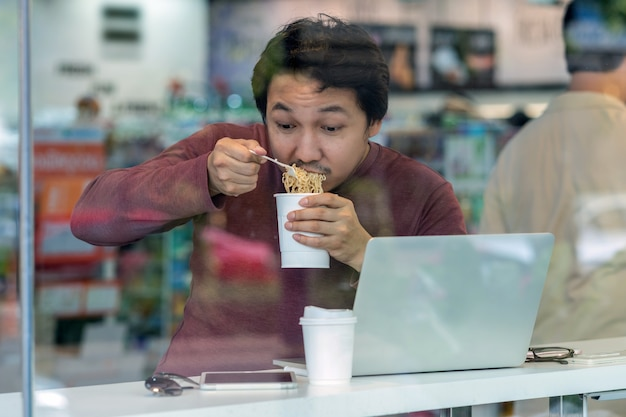 Asian businessman in casual suit eating noodles